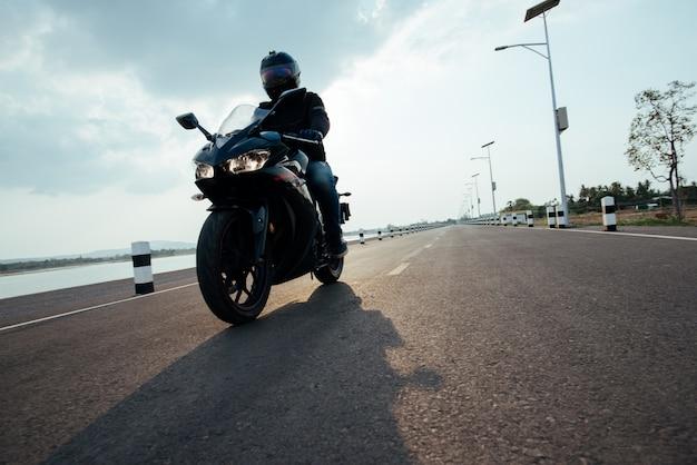 Rider motorbike na equitação da estrada. se divertindo dirigindo a estrada vazia Foto gratuita