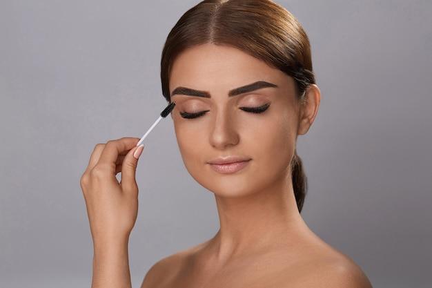 Rímel. maquiagem de beleza, pele macia fresca e cílios grossos pretos longos, aplicar rímel com escova cosmética. extensões de cílios. pestanas falsas. Foto Premium