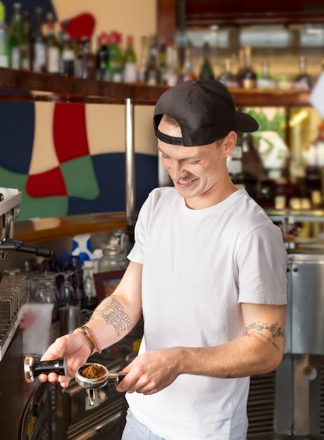 Rindo alegre barista ou barman segurando portafilter cheio de café moído. Foto Premium