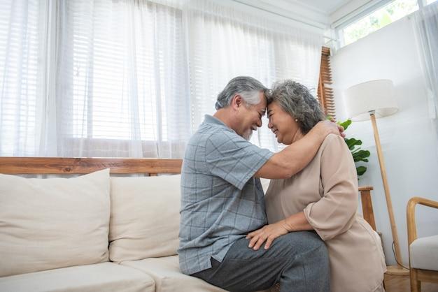 Rindo aposentados casal muito asiático, sentado no sofá em casa, cônjuges, tendo sincero sorriso saudável, serviços de check-up de tratamento odontológico para idosos, conceito de cuidados de saúde seguro médico Foto Premium