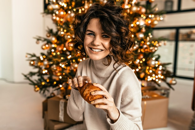 Rindo garota feliz com penteado encaracolado, posando com croissant sobre a árvore de natal com emoções felizes. manhã de ano novo, festa de natal Foto gratuita