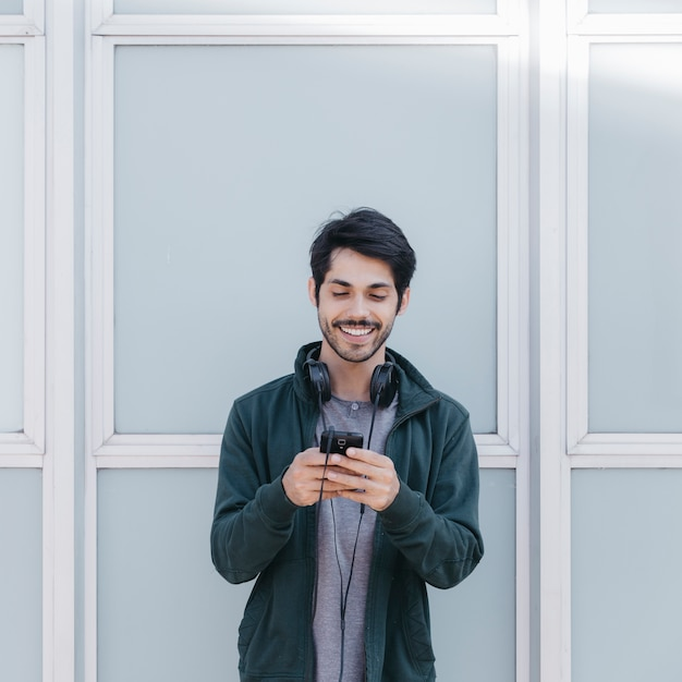 Rindo homem com smartphone fora Foto gratuita