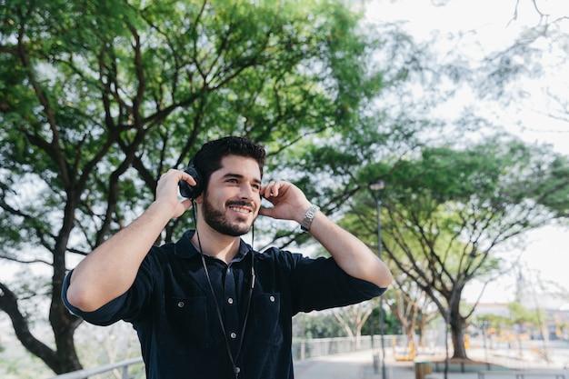 Rindo, homem, desfrutando música nos fones de ouvido Foto gratuita