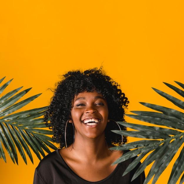 Rindo jovem negra com folhas de palmeira em fundo colorido Foto gratuita