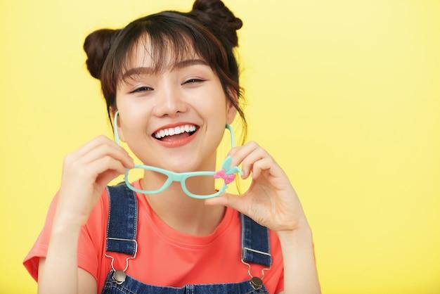 Rindo menina asiática posando no estúdio e segurando os óculos no quadro colorido Foto gratuita