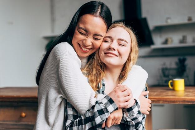 Rindo mulheres abraçando em casa Foto gratuita
