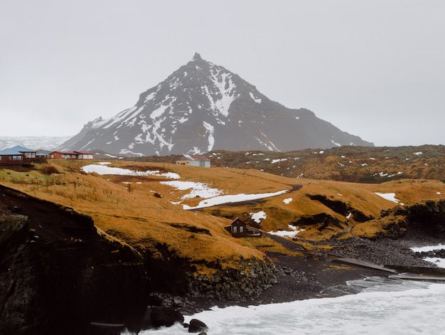 Rio cercado por rochas e colinas cobertas de neve e grama em uma vila na islândia Foto gratuita