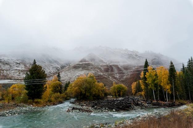 Rio turquesa em um fundo de montanhas cobertas de neve Foto Premium