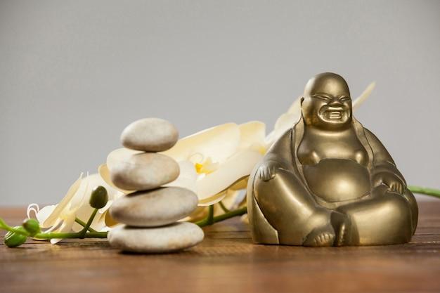 Rir estatueta de buda com seixos de pedra e flor Foto gratuita