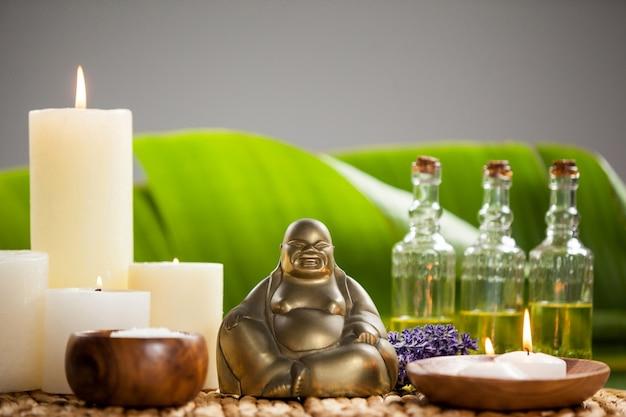 Rir estatueta de buda, vela acesa, frascos de óleo de massagem e sal marinho Foto gratuita