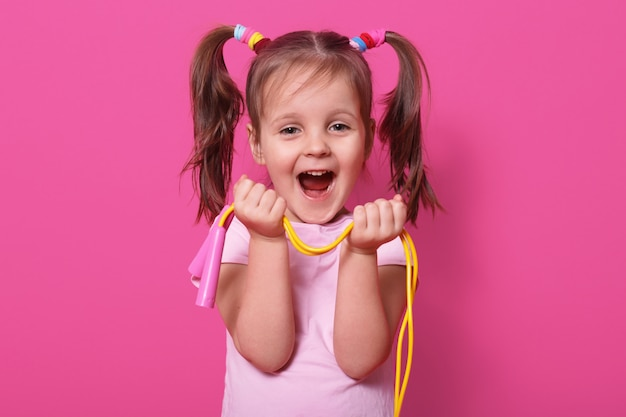Rir linda garota usa rosa t hirt, carrinhos isolados na rosa, mantenha a corda de pular brilhante nas mãos. criança feliz com a boca aberta gosta de brincar com a nova corda de pular. conceito de infância. Foto gratuita