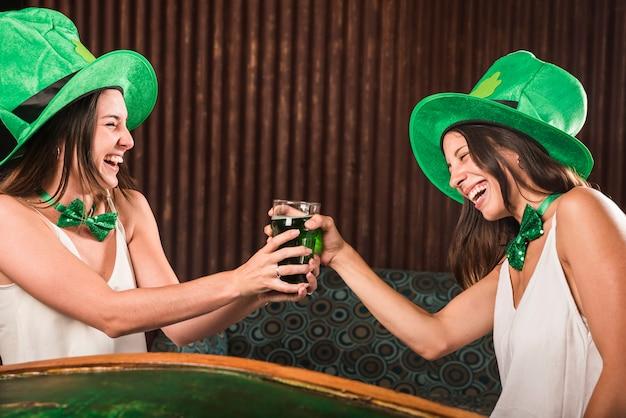Rir, mulheres jovens, copo segurando, de, bebida, ligado, canapé, em, sala Foto gratuita