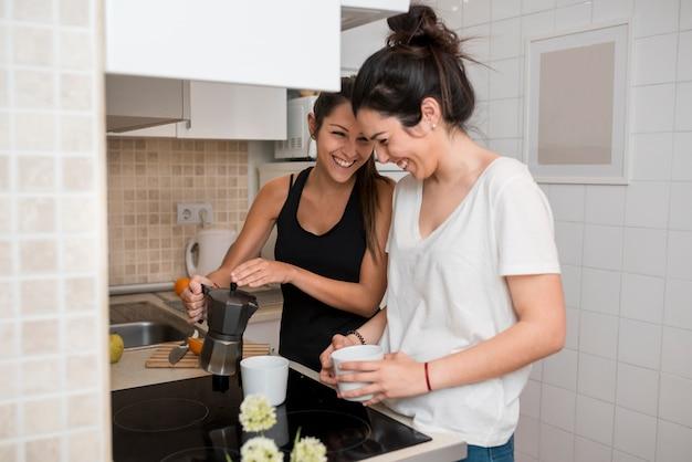 Rir, mulheres jovens, cozinhar, em, cozinha Foto gratuita
