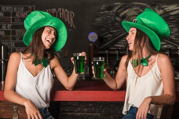 Rir, mulheres jovens, em, são, patricks, chapéus, segurando, copos bebida, em, barra, contador Foto gratuita