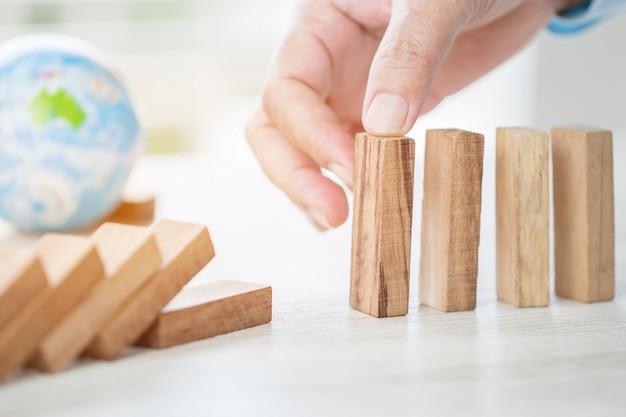 Risco de planejamento de estratégia no conceito de negócio: empresário ou engenheiro colocando dominós de bloco de madeira Foto Premium