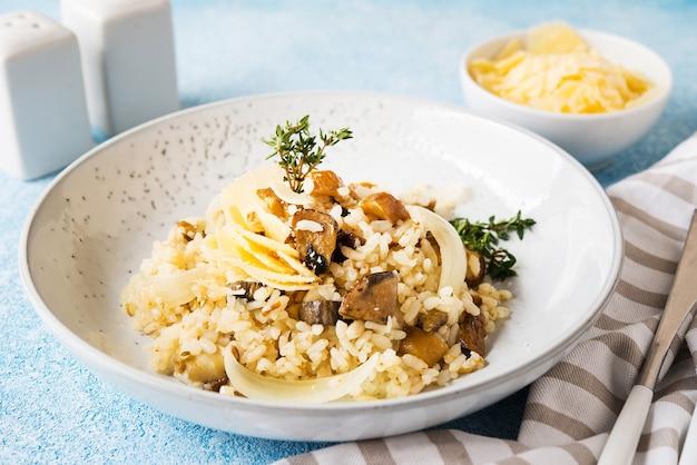 Risoto com cogumelos silvestres brancos e parmesão, close-up Foto Premium