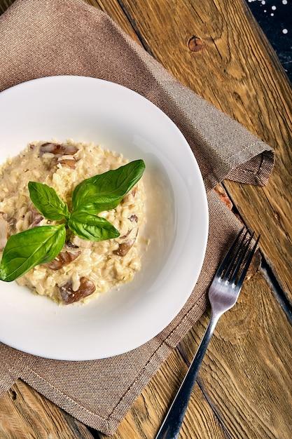 Risoto de cogumelo italiano tradicional caseiro na mesa de madeira Foto Premium