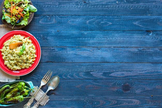 Risoto vegetariano com vários vegetais, na mesa rústica de madeira. Foto Premium