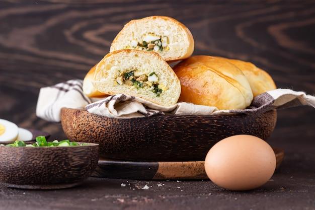 Rissóis cozidos frescos com ovo e recheio de cebola verde. tradicional russo e ucraniano pirozhki salgado. Foto Premium