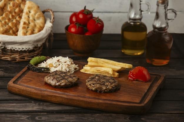Rissóis de carne grelhados servidos com arroz, batata frita, tomate e pimenta grelhados Foto gratuita