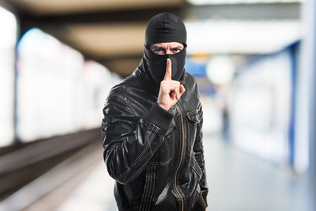 Robber fazendo um gesto de silêncio Foto gratuita