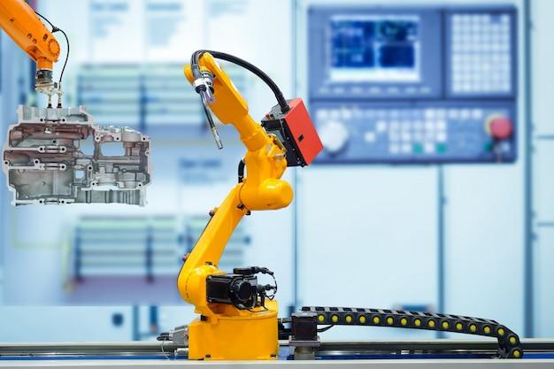 Robô de soldagem em movimento e robô emocionante trabalhando com peças de motor de moto na fábrica inteligente turva azul Foto Premium