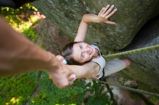Rockclimber ajudando a alpinista feminina para chegar ao topo da montanha Foto Premium