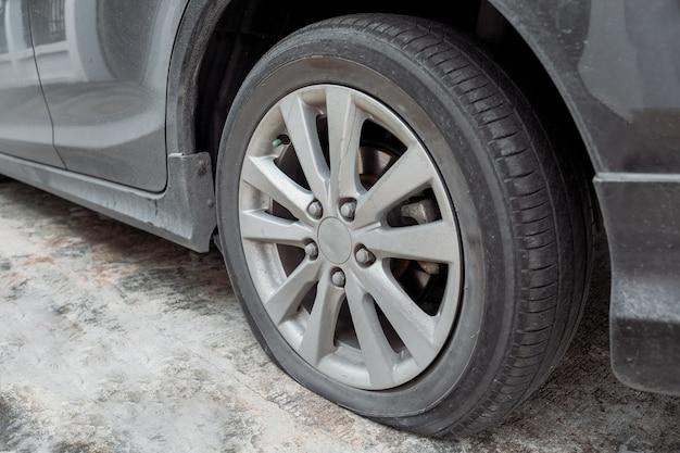 Roda de carro com pneu liso e vazamento de ar do acidente. Foto Premium