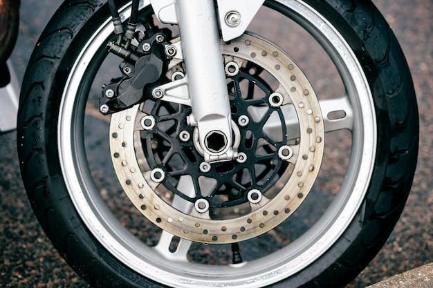 Roda de motocicleta com sistema de freios a disco e raios de metal. foto detalhada closeup de forquilhas e pneus de moto. transporte. tecnologias modernas de direção Foto Premium