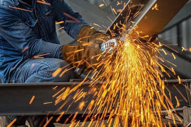 Roda elétrica de moagem em estrutura de aço e soldadores com múltiplas faíscas na fábrica. Foto Premium