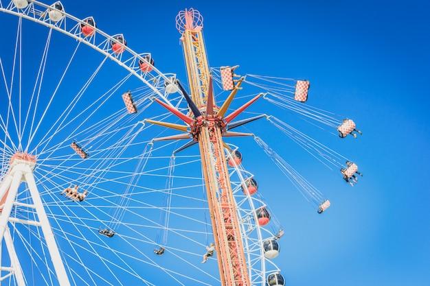 Roda-gigante e carrossel com correntes em um parque de diversões Foto Premium