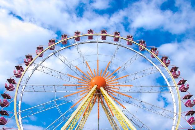 Roda gigante sobre o céu azul com nuvens brancas Foto Premium