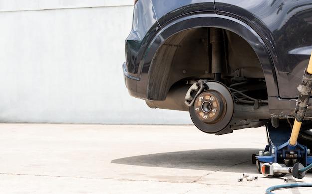 Roda nova ao ar livre do pneu que substitui, reparo do pneu de carro do acidente que repara o serviço usando o jaque e a chave de fenda elétrica Foto Premium