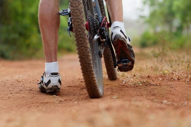 Roda traseira de bicicleta de montanha e pé de cavaleiros. tiro traseiro da bicicleta de montanha na estrada de terra marrom. feche acima da vista de um pneu de bicicleta de montanha. Foto Premium