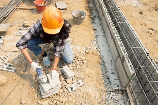 Rodada de serra nas mãos do construtor, trabalhar na colocação de lajes de pavimentação. Foto gratuita