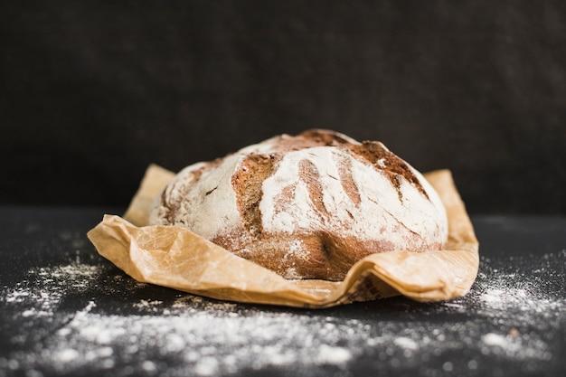Rodada recém-assados centeio rústico pão redondo no papel marrom contra o fundo preto Foto gratuita
