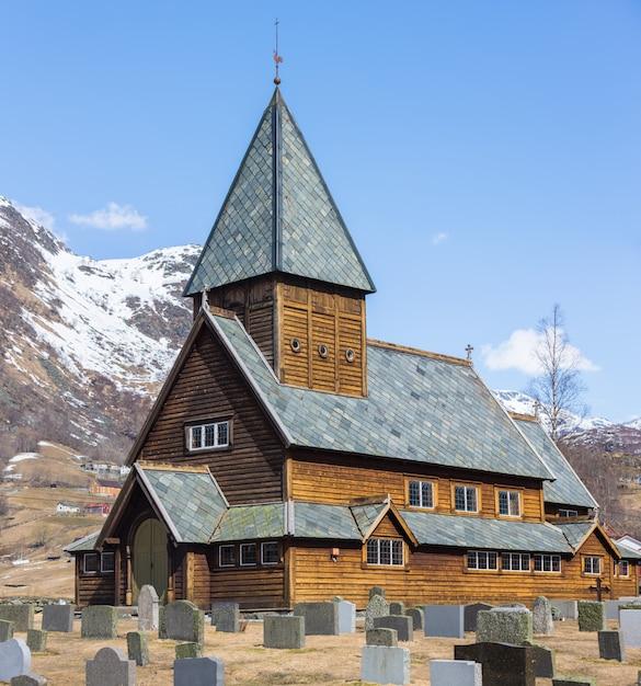 Roldal stave church (roldal stavkyrkje) com fundo de montanha de boné de neve Foto Premium