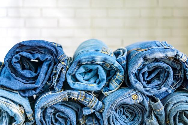 Role as calças de brim azuis dispostas na pilha na parede. conceito de roupas de moda e beleza Foto Premium