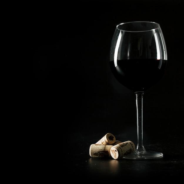 Rolhas perto de um copo de vinho Foto gratuita