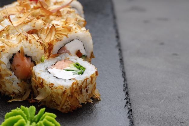 Rolinho de sushi com raspas de atum no prato close up Foto Premium