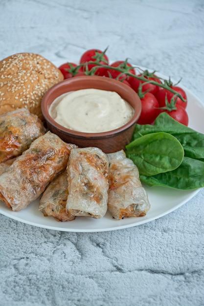 Rolinho primavera com carne e legumes, servidos em um prato branco com molho Foto Premium