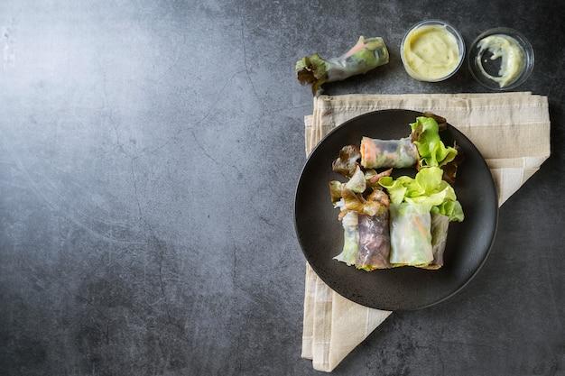 Rolinho primavera de vegetais frescos, alimentos limpos, salada para perda de peso, em fundo escuro Foto Premium
