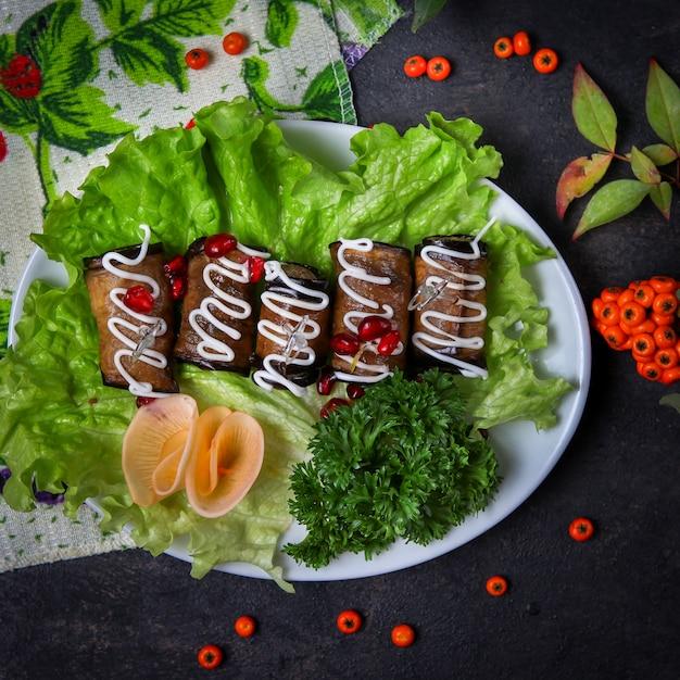 Rolinhos de berinjela em um prato com ervas, maionese, queijo, frutas, folhas Foto gratuita