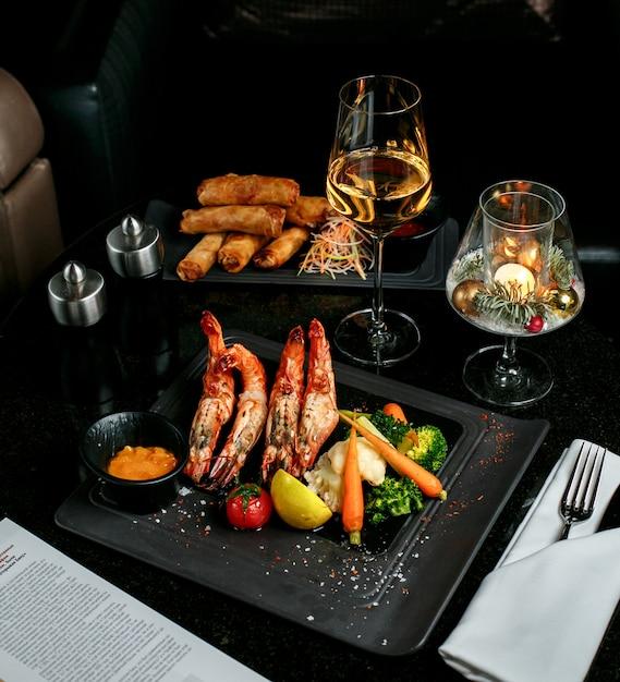 Rolinhos de camarão frito e legumes com shampaigne Foto gratuita