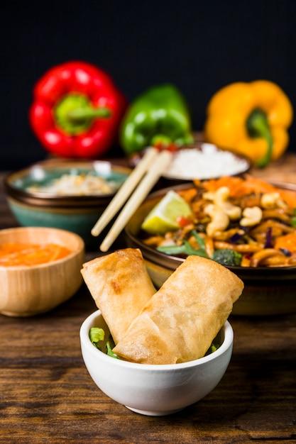 Rolinhos de primavera frito em tigela branca com comida tailandesa na mesa de madeira Foto gratuita