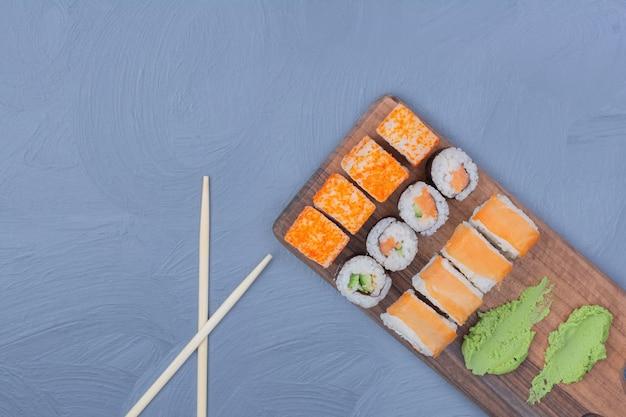 Rolinhos de saquê maki e philadelphia com molho de wasabi em uma travessa de madeira Foto gratuita