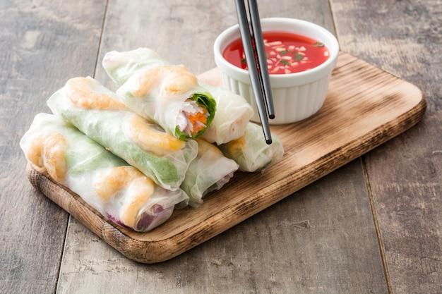 Rolinhos vietnamitas com legumes, macarrão de arroz e camarão com molho de pimentão doce na superfície de madeira Foto Premium