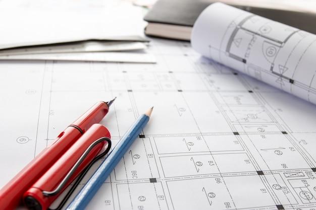 Rolls de plantas da arquitetura e planos da casa nas ferramentas de desenho da tabela e do arquiteto. Foto Premium