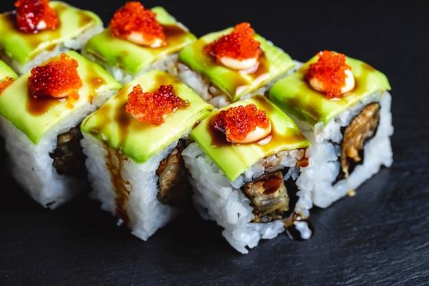 Rolo de dragão verde de vista lateral com molho de soja de abacate de peixe frito e caviar tobiko por cima Foto gratuita