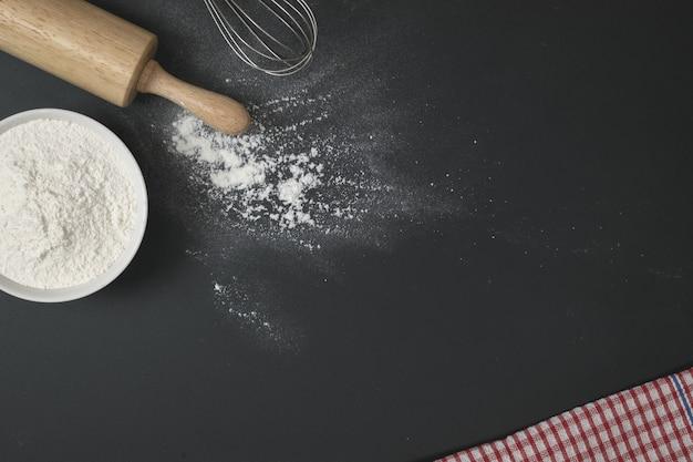 Rolo de massa de madeira, uma xícara de farinha e bata na mesa preta com farinha Foto Premium